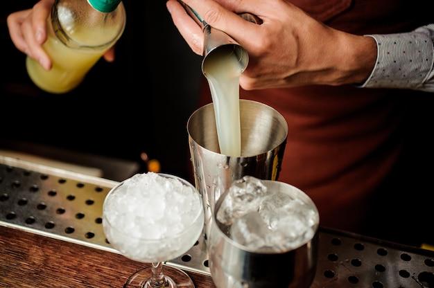 Barkeeper, der einen saft für die herstellung eines alkoholischen cocktails gießt