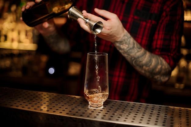 Barkeeper, der einen trinidad swizzle-cocktail aus dem stahl-jigger in das glas auf der bartheke einschenkt