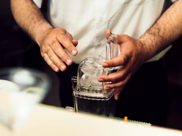 Barkeeper, der eis in kasten für das schleifen einsetzt