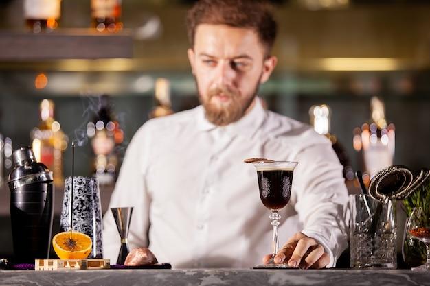 Barkeeper, der kaffeecocktail in der lounge-bar präsentiert. gute atmosphäre