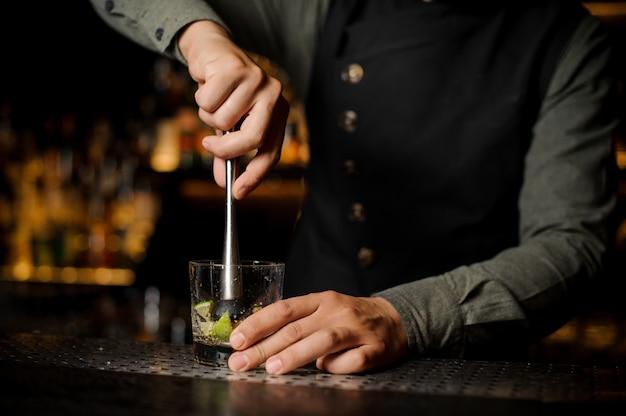 Barkeeper, der saft vom frischen kalk unter verwendung der zitrusfruchtpresse zusammendrückt