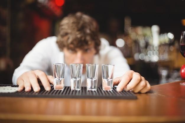 Barkeeper, der schnapsgläser für alkoholische getränke auf der bartheke vorbereitet und auskleidet