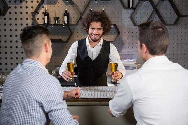 Barkeeper, der seinen kunden bier serviert
