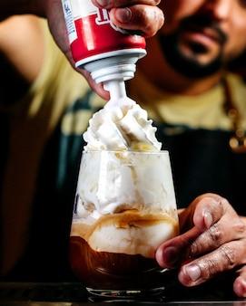Barkeeper der vorderansicht, der ein dessert mit schlagsahne vorbereitet