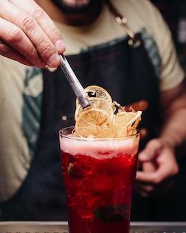 Barkeeper der vorderansicht, der ein rotes getränk vorbereitet