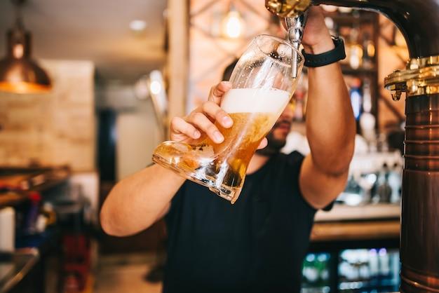 Barkeeper-fassbier vom fass im bierglasstiefel.