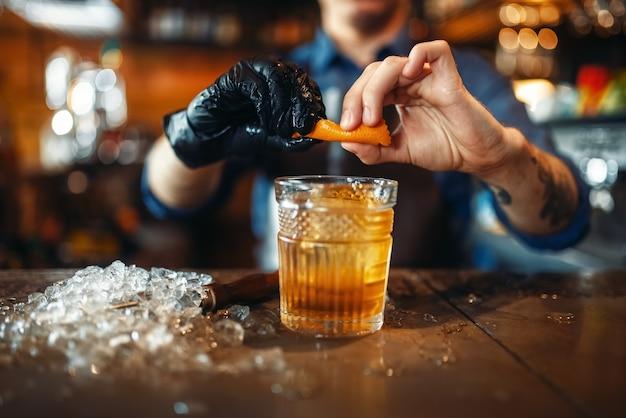 Barkeeper fügt dem alkoholischen getränk orangenschalen hinzu