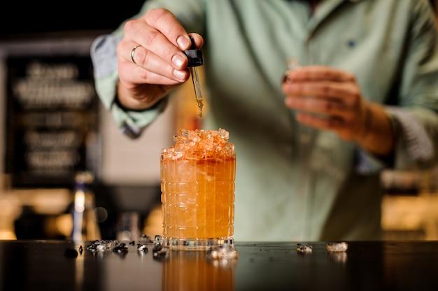 Barkeeper fügt dem cocktail bitter hinzu