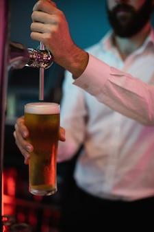 Barkeeper füllt bier aus barpumpe