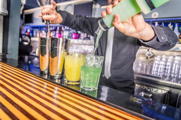 Barkeeper gießt alkohol aus der flasche und dem shaker