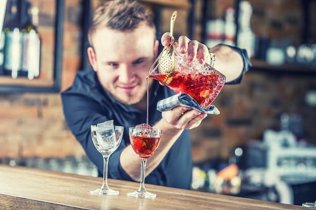 Barkeeper gießt alkoholisches cocktailgetränk manhattan barman in der kneipe, die ein cocktailgetränk zubereitet