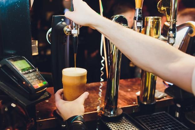 Barkeeper gießt aus dem fass frisches bier in das glas in der kneipe.