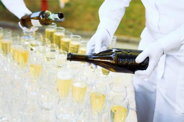 Barkeeper gießt champagner in gläser