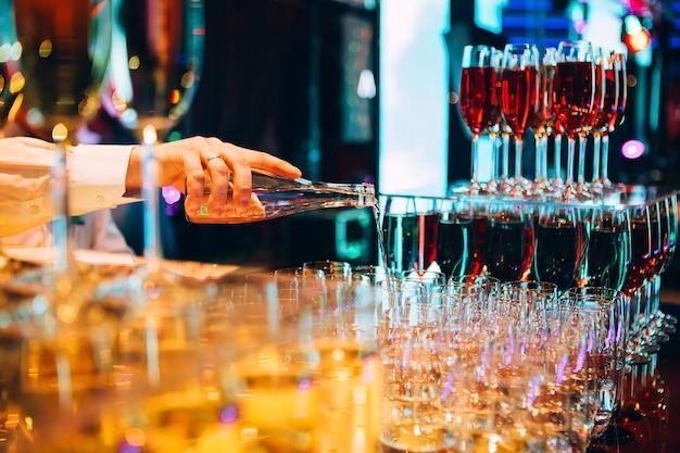 Barkeeper gießt champagner. kellner gießt champagner auf einer party.
