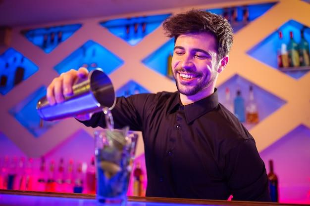 Barkeeper gießt cocktail in glas