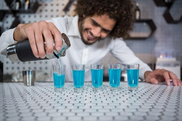 Barkeeper gießt cocktail in schnapsgläser