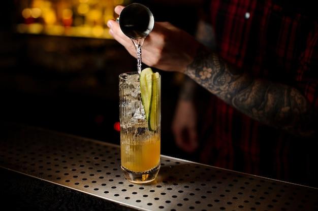 Barkeeper gießt drink ein und macht einen lynchburg-limonade-cocktail aus dem stahl-jigger in das glas auf der bartheke