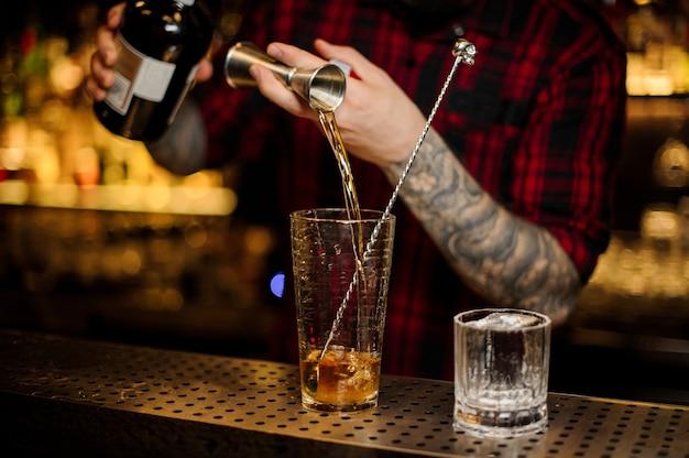 Barkeeper gießt drink ein und macht einen rusty nail cocktail vom stahl-jigger bis zum glasmessbecher auf der bartheke