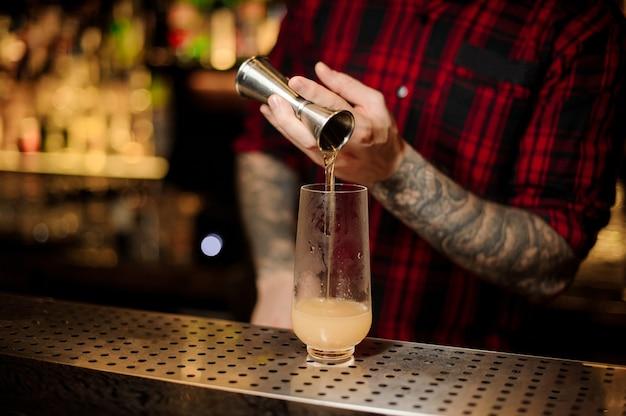 Barkeeper gießt eine portion alkoholisches getränk mit jigger in ein cocktailglas auf der bar