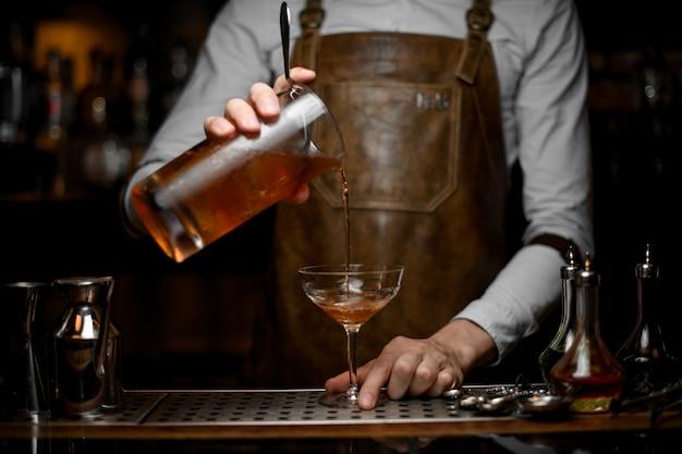 Barkeeper gießt einen alkoholcocktail aus sieb