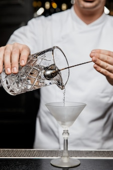 Barkeeper gießt einen cocktail aus einem mischglas in ein martini-glas