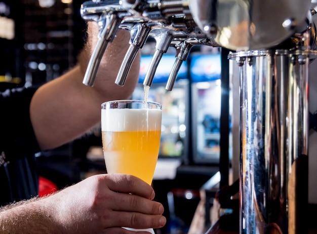 Barkeeper gießt fassbier auf gläser in der bar. restaurant.