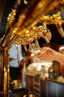 Barkeeper gießt frisches bier in ein glas. freunde entspannen sich an der theke in der bar, nachtleben. gruppe von menschen entspannen in der kneipe, nachtlebensstil, freundschaft, ereignisfeier
