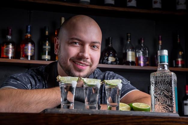 Barkeeper gießt harten spiritus in kleine gläser