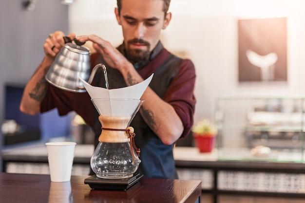 Barkeeper gießt heißes wasser in den filter mit geröstetem kaffee