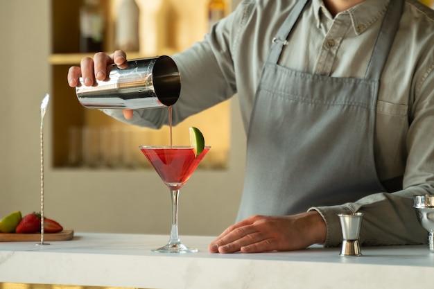 Barkeeper gießt kosmopolitischen cocktail in martini-glas