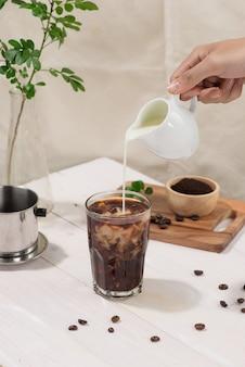 Barkeeper gießt milch in ein glas kaffee