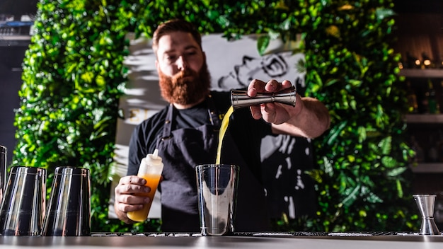 Barkeeper gießt saft ein