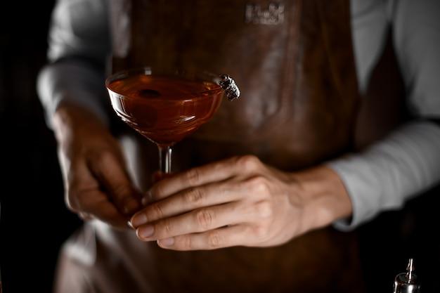 Barkeeper hält cocktail mit oliven