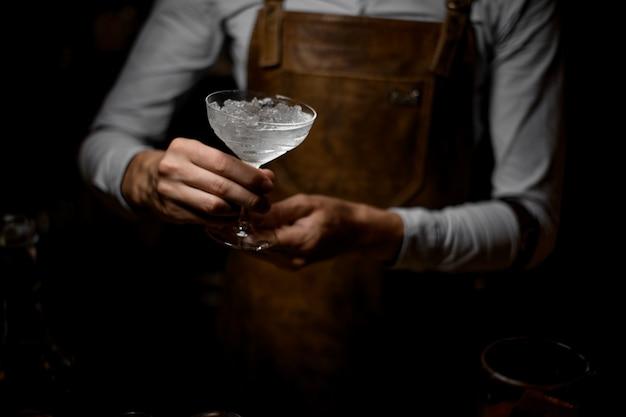 Barkeeper hält glas mit einem geschmolzenen eis
