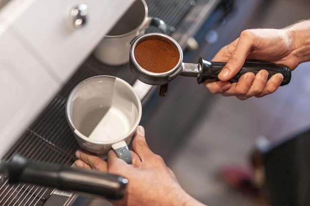 Barkeeper hält tasse und siebträger mit gemahlenem kaffee