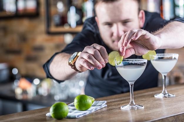 Barkeeper im pub oder restaurant bereitet ein cocktailgetränk margarita zu.