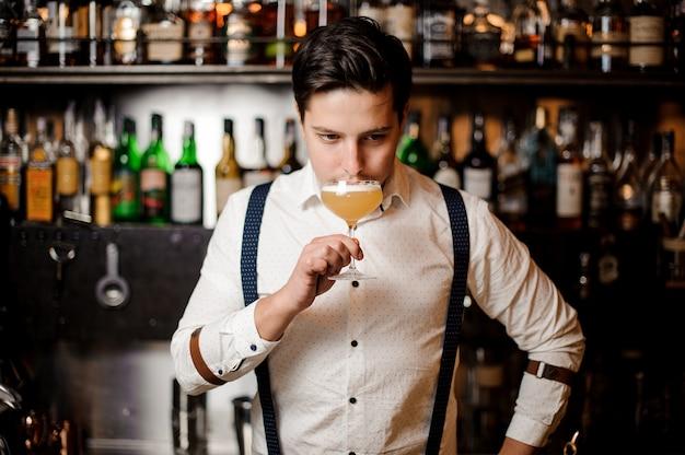 Barkeeper im weißen hemd mit dem cocktail an der bar stehen