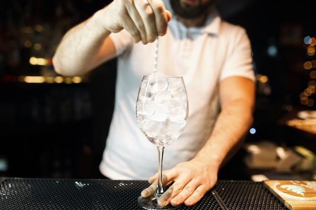 Barkeeper im weißen t-shirt an der bar oder in einem nachtclub und macht einen alkoholischen cocktail. lebensstil