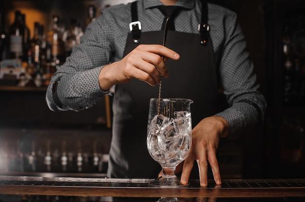 Barkeeper in der schürze eiswürfel mit hilfe des löffels rühren