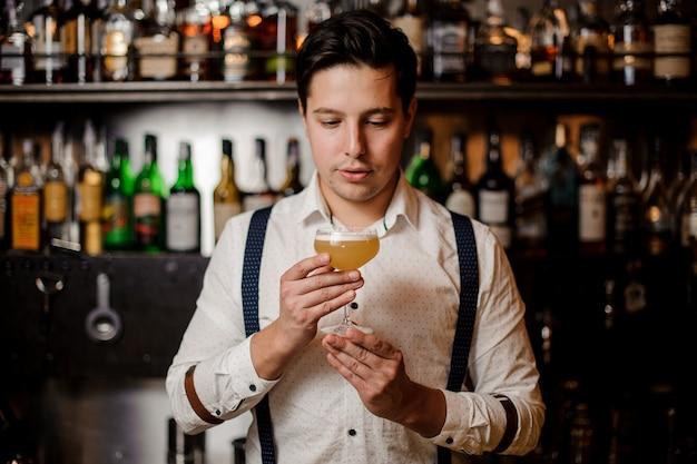 Barkeeper in weißem hemd hält cocktail an der bar stehen
