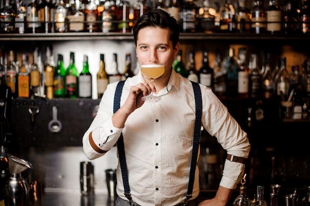 Barkeeper in weißem hemd mit cocktail an der bar stehen