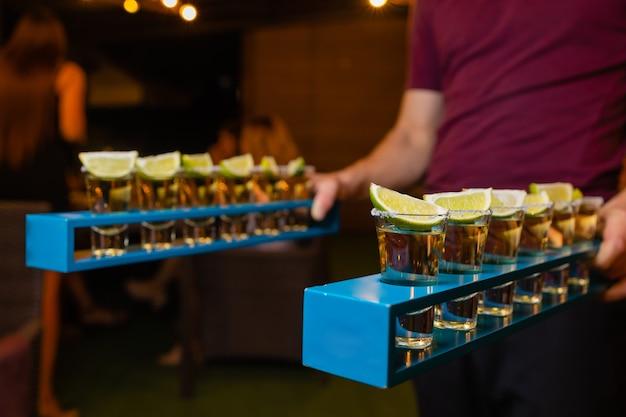 Barkeeper machen alkoholische shots mit rum und schnaps.