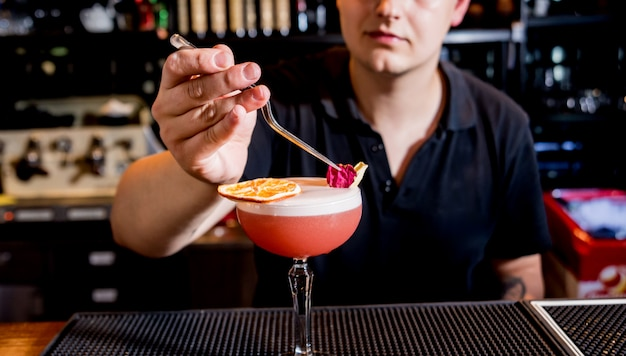 Barkeeper macht cocktail an der theke. frische cocktails. barmann bei der arbeit.