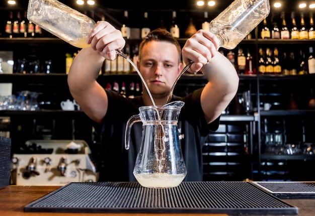Barkeeper macht cocktail an der theke. frische cocktails. barmann