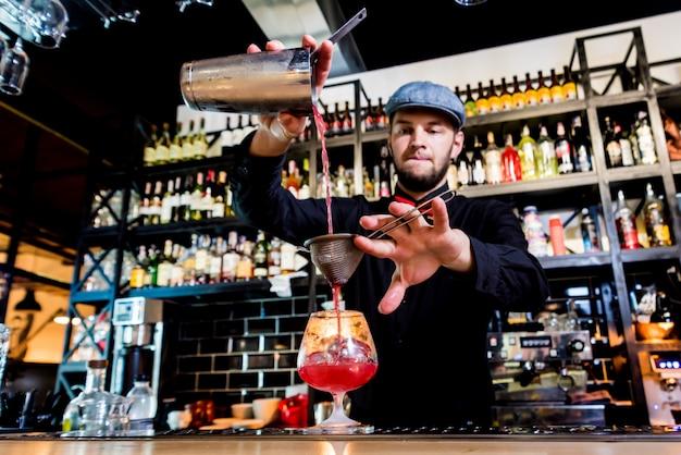 Barkeeper macht cocktail an der theke. frische cocktails.