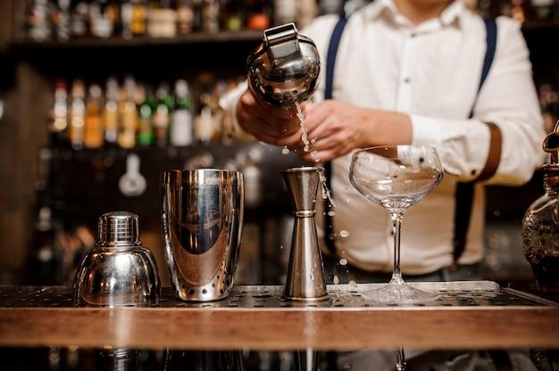 Barkeeper macht ein cocktail an der theke kein gesicht