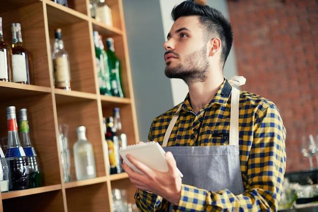 Barkeeper macht eine bestandsaufnahme der produkte
