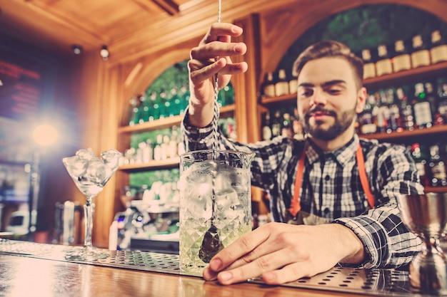 Barkeeper macht einen alkoholischen cocktail an der theke an der bar