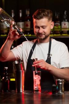 Barkeeper macht einen cocktail mit einem shaker