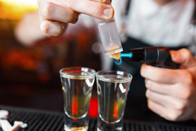 Barkeeper mann, der leckere alkoholschüsse in der kneipenbar mit einem professionellen brenner macht. der barkeeper zündet ein feuerzeug über einem glas an. ruhen sie sich in einem nachtclub aus. nachtparty. nahaufnahme